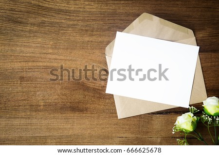 Top view of envelope and blank greeting card with rose flowers on white wooden background. #666625678
