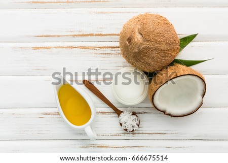 Coconut with coconut oil on white wooden table background. Good for package design element #666675514