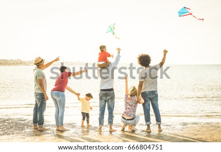 Happy families group with parents and children playing with kite at beach vacation - Summer joy happiness concept with mixed race people having fun together at sunset  - Warm vintage backlight filter #666804751