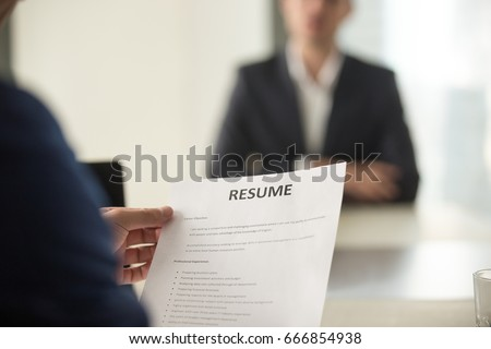 Close up view of job interview in office, focus on resume writing tips, employer reviewing good cv of prepared skilled applicant, recruiter considering application, hr manager making hiring decision  #666854938