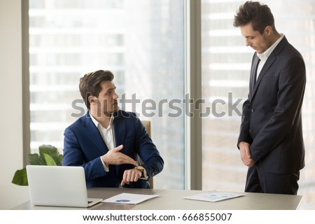 Male subordinate receiving reprimand from boss for being too late at meeting, company director scolding unpunctual manager for missing deadline or not finishing work on time, pointing on wristwatch  Royalty-Free Stock Photo #666855007