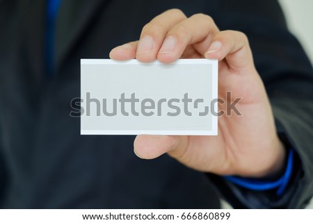 Businessman in black suit showing business card with left hand on gray background. #666860899