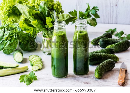 Detox diet. Two small bottles of fresh green smoothies with ingredients on a light wooden background. #666990307