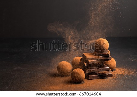 Chocolate candy truffle with chocolate pieces and flying cocoa powder on a dark background #667014604