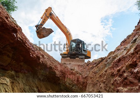 Excavator digging a trench. Work on the construction site. #667053421