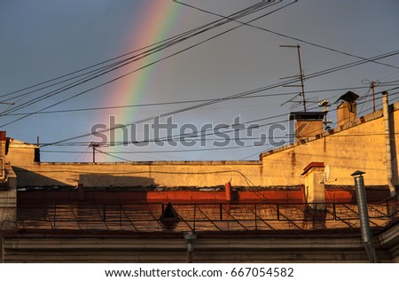 Rainbow over the roof, wires, chimneys #667054582