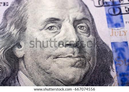 Close up of Benjamin Franklin face on 100 US dollar bill #667074556