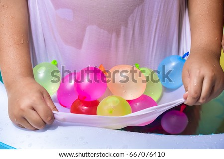 Colorful water balloons in shirt prepare to fight.