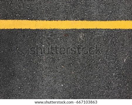 Yellow paint line on black asphalt road surface texture. space transportation background #667103863