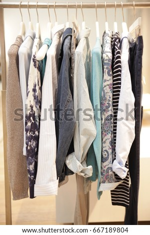 colorful blouses hanging on a clothes rod #667189804