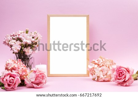 Empty white frame, pink carnations in glass vases, pink roses, beige hydrangea and scented candle on pink background. Sweet and romantic interior. Wedding's background.