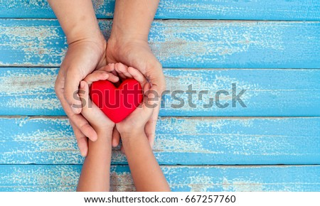 Red heart in child kid and mother hands on old blue wooden table in vintage retro style #667257760