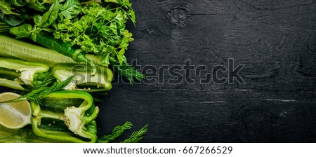 A large set of green vegetables on a wooden background. Top view. Free space. #667266529