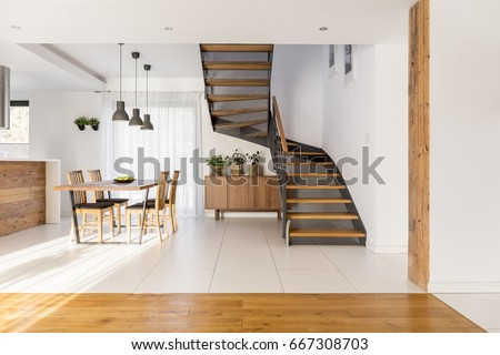 Open space with industrial half-landing stairs and wooden dining area