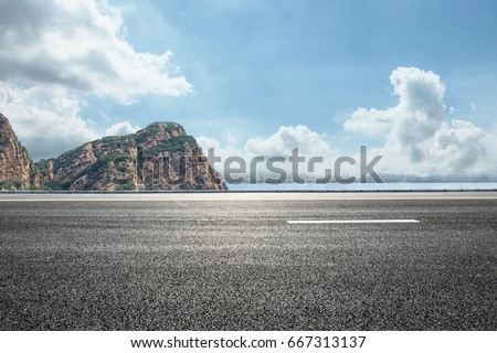 asphalt road and mountain under the blue sky