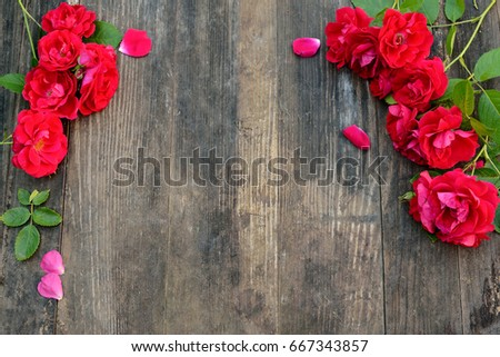 Frame of red roses on a wooden background with space for text. Flat lay #667343857