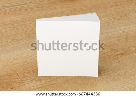 Blank white square soft cover book standing on wooden background. Isolated with clipping path around book. 3d illustration #667444336