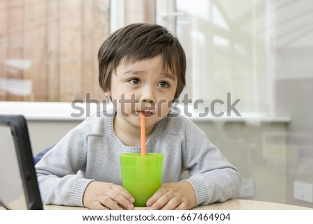 Happy boy sitting in playroom and enjoy drinking smooth orange in plastic green glass while watching TV, copy space #667464904