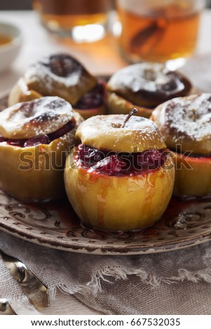 Vertical photo of a brown plate of baked apples with cranberries #667532035