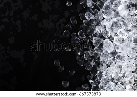Crushed ice background. Pieces of crushed ice cubes on black background. Copy space, top view