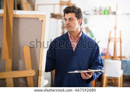 Happy art painter holding artist palette and painting on canvas #667592680