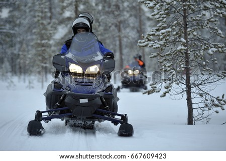 FINLAND - INARI - Caravan of tourists with snowmobiles on the snow - snowcat in North Pole #667609423
