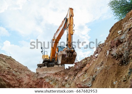 Excavator digging a trench. Work on the construction site. #667682953