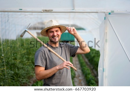 Portrait of young man in front of a greenhouse. Young entrepreneur. #667703920