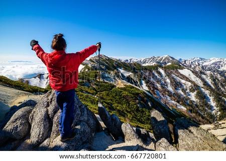Successful woman trekker hiking at Mount Tsubakuro Dake, famous trekking mountain in Azumino, Nagano, Japan. It is situated in Japan's Hida Mountains or Japan Alps.  #667720801