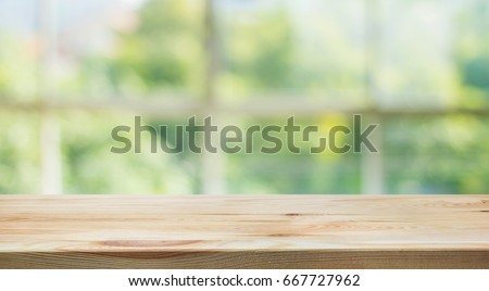 Wood table top on blur of window glass and abstract green from garden background. #667727962