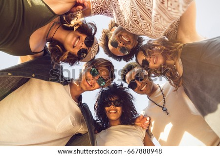 Multiethnic group of friends huddle join in a circle and looking down outdoors #667888948