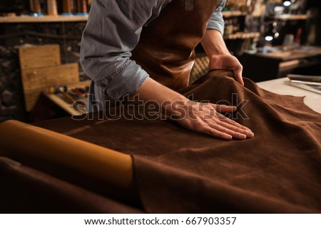 Close up of a male shoemaker working with leather textile at his workshop #667903357