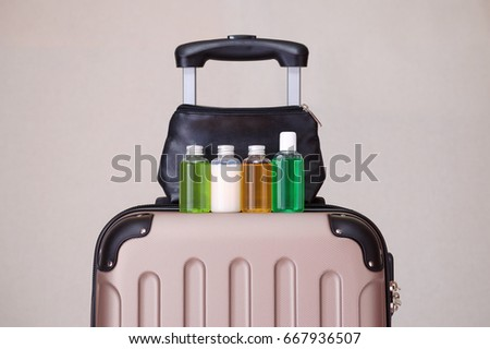 travel toiletries, small plastic bottles of hygiene products on the suitcase and cosmetic bag Royalty-Free Stock Photo #667936507