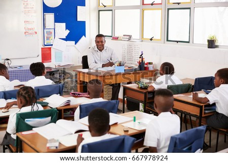 Teacher and kids sitting at desks in elementary classroom #667978924