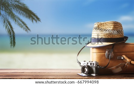 Vintage suitcase, hipster hat, photo camera and passport on wooden deck. Tropical sea, beach and palm three in background. Summer holiday traveling concept design banner with copyspace.