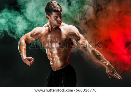 Handsome man with muscular topless body holding arm down. Smoke. Isolated. #668016778