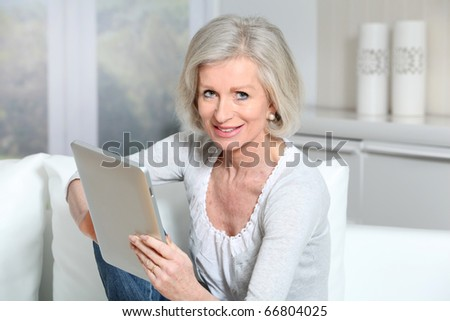 Closeup of senior woman sitting on sofa with electronic pad #66804025