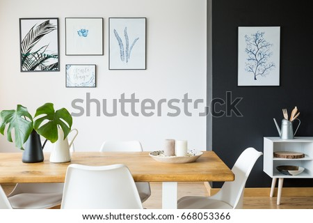 Black and white dining room with wooden table and posters #668053366