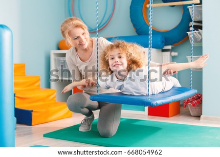 Woman helping a smiling boy to exercise on a therapy swing #668054962