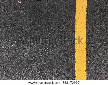 Yellow paint line on black asphalt road surface texture. space transportation background #668172997