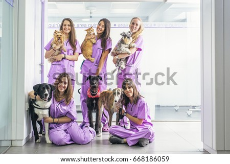 Cheerful women team veterinary holding her pets. Veterinary Concept. #668186059