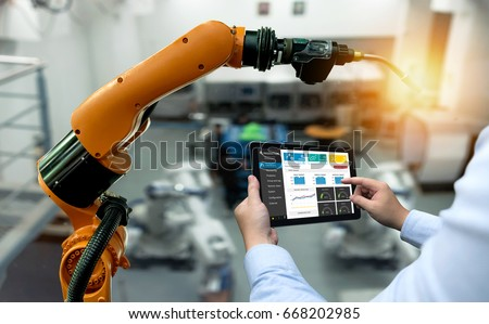 Engineer hand using tablet, heavy automation robot arm machine in smart factory industrial with tablet real time monitoring system application. Industry 4th iot concept. #668202985