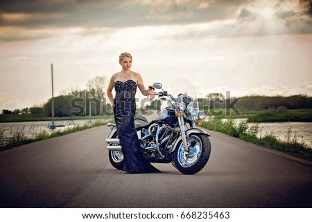 Pretty young lady in a classic black gown and motorcycle at sunset on highway #668235463