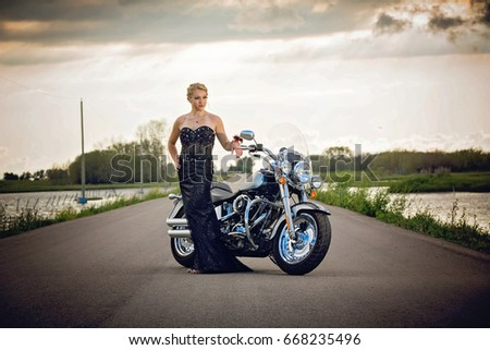 Pretty young lady in a classic black gown and motorcycle at sunset on highway #668235496