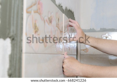 Tilers hands are installing a ceramic tile on a wall in a bathroom. #668241226