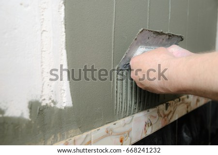 Tilers hands are putting on a tile adhesive on the wall in the bathroom. #668241232