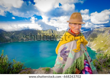 QUITO, ECUADOR - NOVEMBER, 25 2016: Unidentified indigenous old woman wearing a typical andean clothes in front of the Quilotoa lake with a beautiful magenta color of the Quilotoa caldera. Quilotoa is #668263702