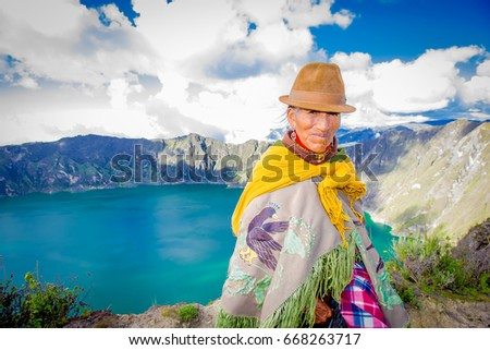 QUITO, ECUADOR - NOVEMBER, 25 2016: Unidentified indigenous old woman wearing a typical andean clothes in front of the Quilotoa lake with a beautiful magenta color of the Quilotoa caldera. Quilotoa is #668263717