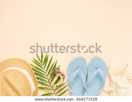 Summer fashion, summer outfit on cream background. Blue flip flops, seashell, wood bracelet and straw hat. Flat lay, top view
