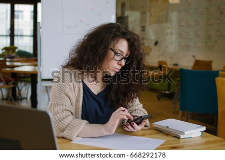 Young woman working in the office and using phone #668292178